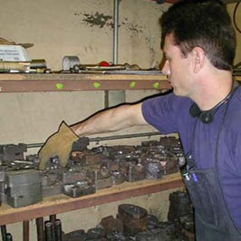 Cathouse Employee selecting iron mold casting from an inventory of over 200 castings